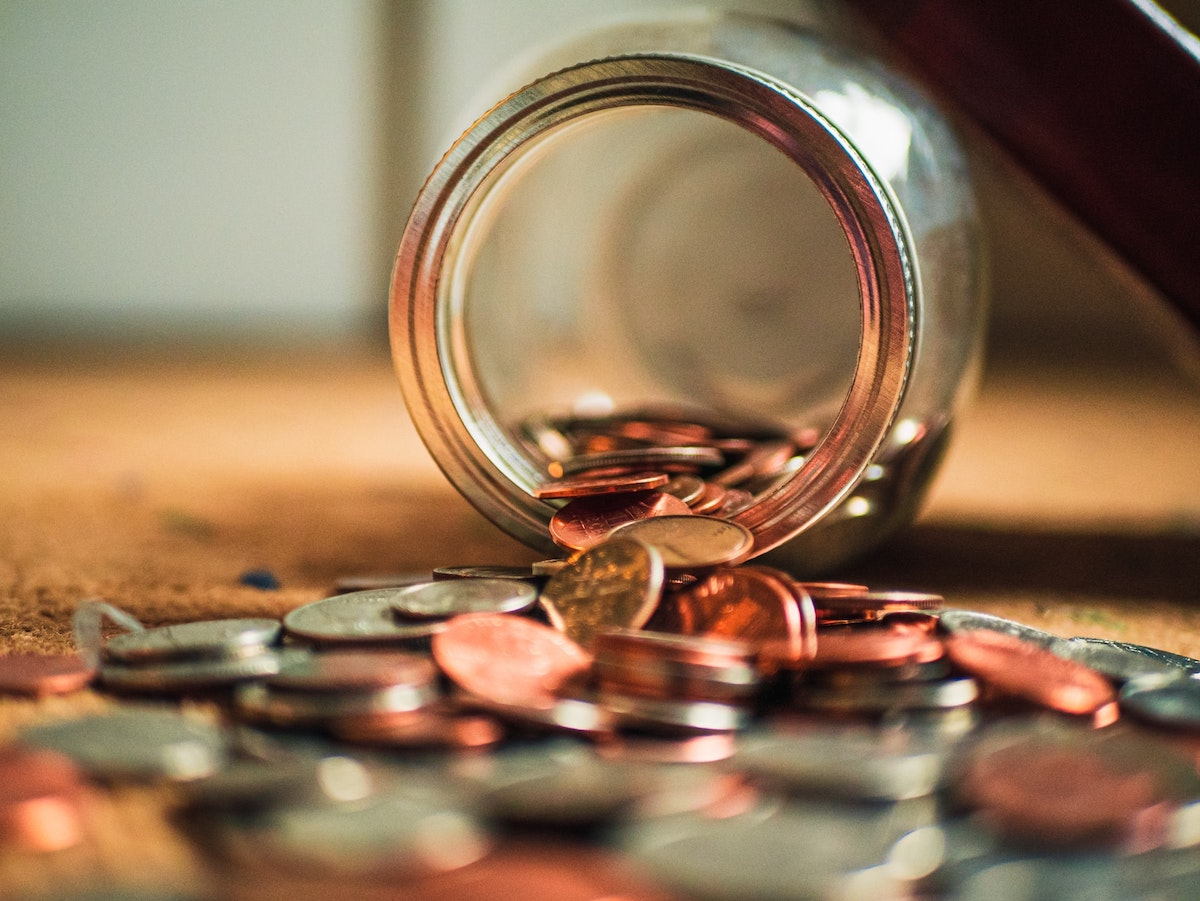 jar of coins falling out on wood desk for a wage and hour attorney